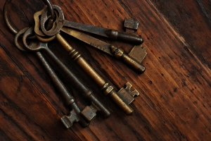 Antique skeleton keys on rustic dark wood background.  Low key s
